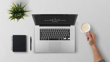 flat lay of macbook on desk and person holding coffee cup | Website Copywriting