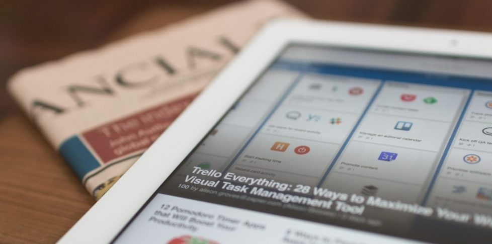 Close up of ipad with the tile of an article next to a copy of the financial times | Article Writing